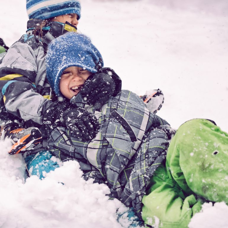 Children Sledding Together Laughing During A Storm